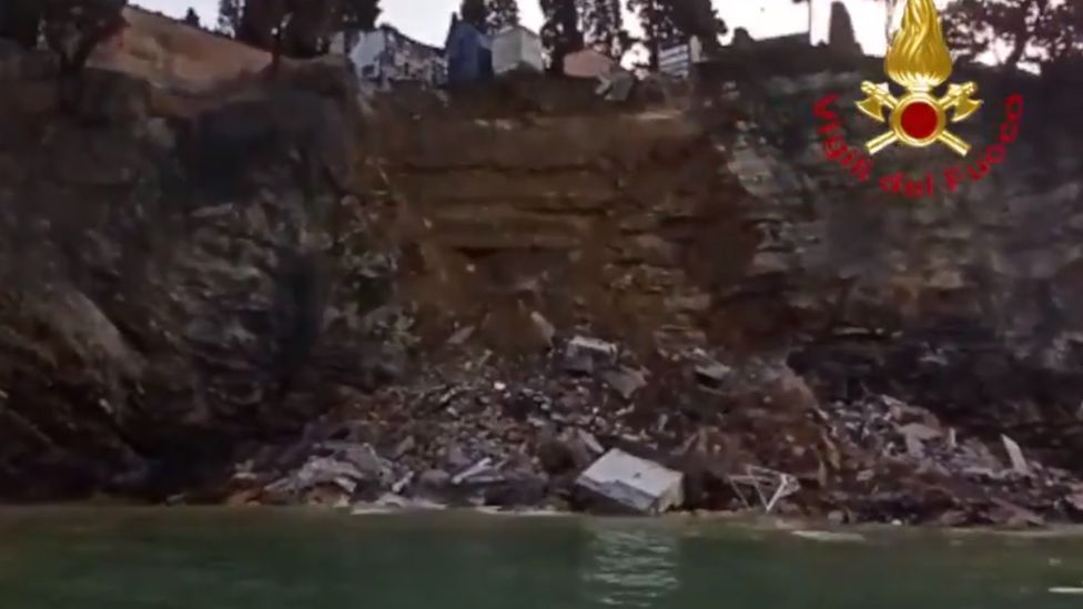 Photos of the collapsed cliff show coffins and debris in the water