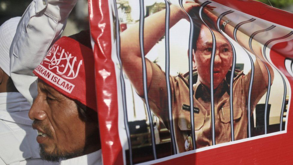 """A Muslim protester holds a banner with picture depicting Jakarta Governor Basuki Tjahaja Purnama, popularly known as """"Ahok,"""" behind bars during a rally outside the court where his trial hearing of is held in Jakarta, Indonesia, on 20 December 2016"""
