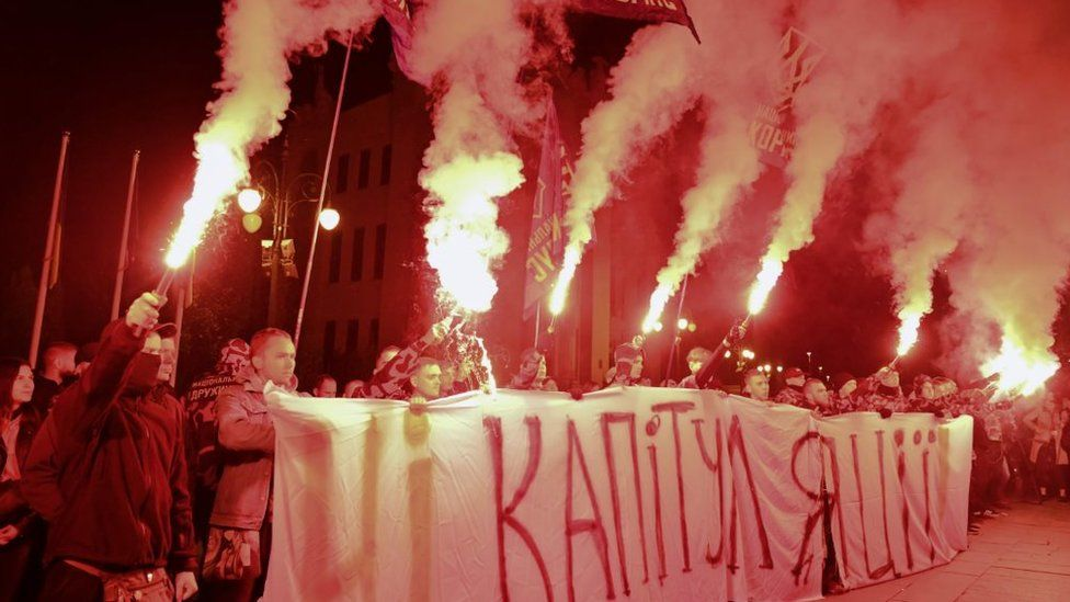 Ukrainian nationalists burn flares and hold banner reading No to capitulation on 1 October
