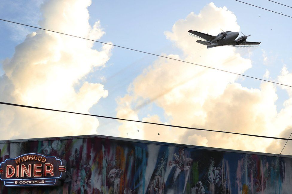 A plane sprays pesticide over the Wynwood neighbourhood in the hope of controlling and reducing the number of mosquitoes, some of which may be capable of spreading the Zika virus on August 6, 2016 in Miami, Florida