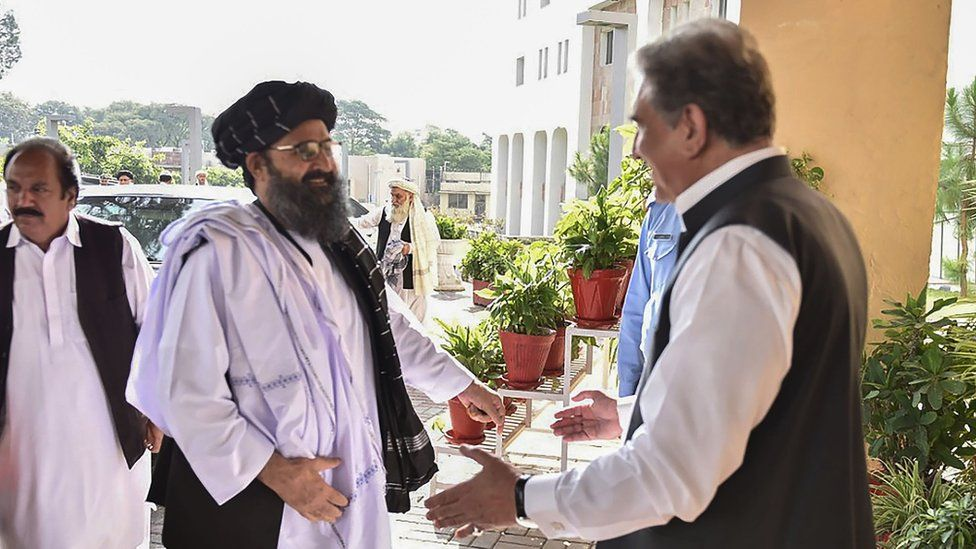 Pakistan's Foreign Minister Shah Mehmood Qureshi greets Taliban co-founder Mullah Baradar upon his arrival with delegation at the Pakistan Foreign Ministry in Islamabad.