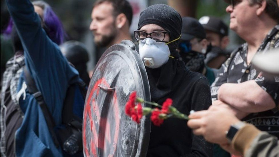 An anti-Trump demonstrator protects herself with a homemade shield during the rally at Chapman Square in downtown Portland (04 June 2017)