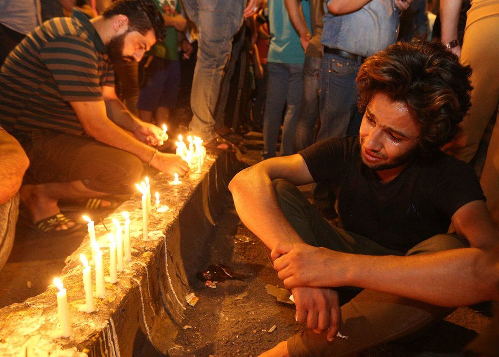 People light candles at the scene of a massive car bomb attack in Karada, Baghdad, 4 July