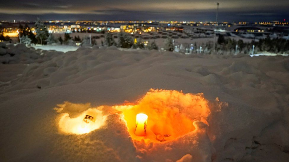 Candles are laid in snow at Ask on 2 January 2021