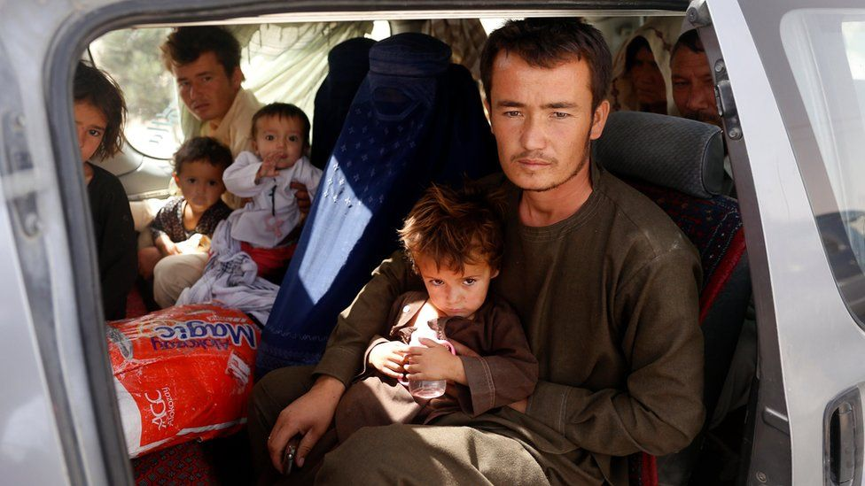 An Afghan family, who have escaped from the volatile city of Ghazni province, poses for a photograph in the entrance gate of Kabul, Afghanistan, 13 August 2018.
