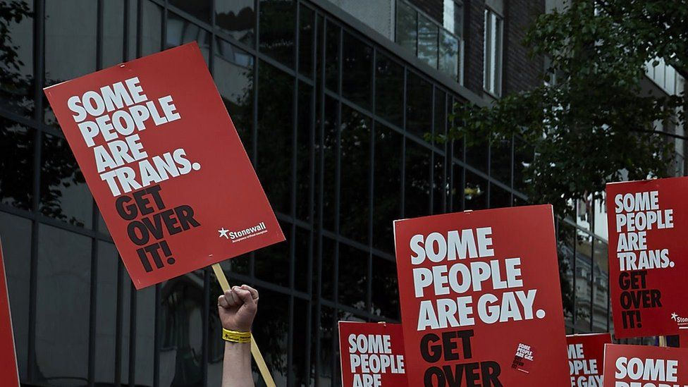 people marching with signs reading 'some people are trans, get over it'