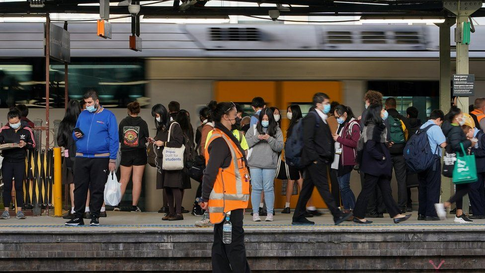 Commuters wear protective face masks on a train platform at Central Station in Sydney