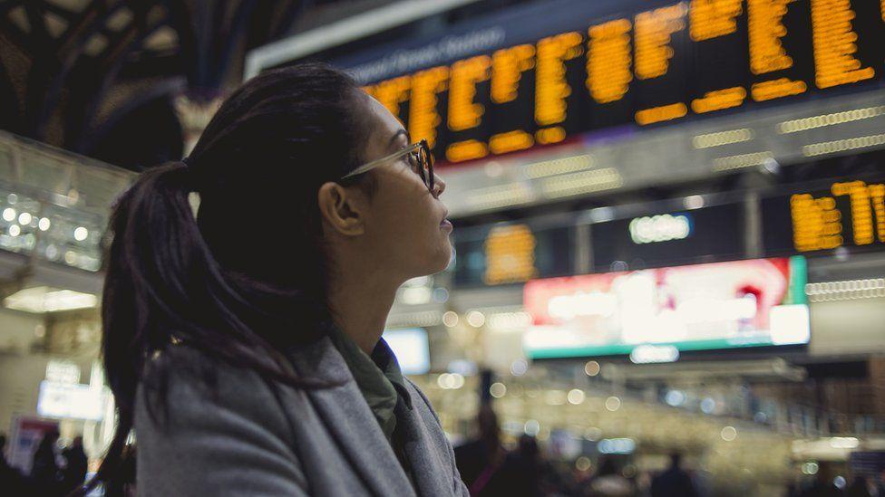 woman looking at rail board