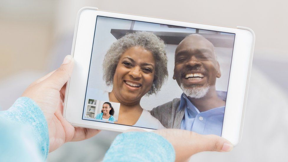 A stock photo shows two older people on a tablet, calling a younger person