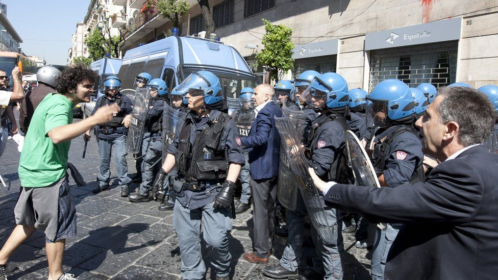 Demonstrators (L) face riot policemen as they try to enter the offices of Equitalia, Italy's tax collection agency during a protest against the government's austerity measures in May 2012