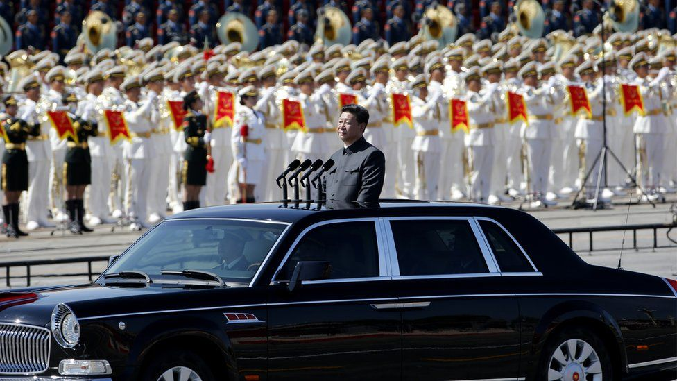 Chinese President Xi Jinping stands in a car to review the army during a parade commemorating the 70th anniversary of Japan's surrender during World War II