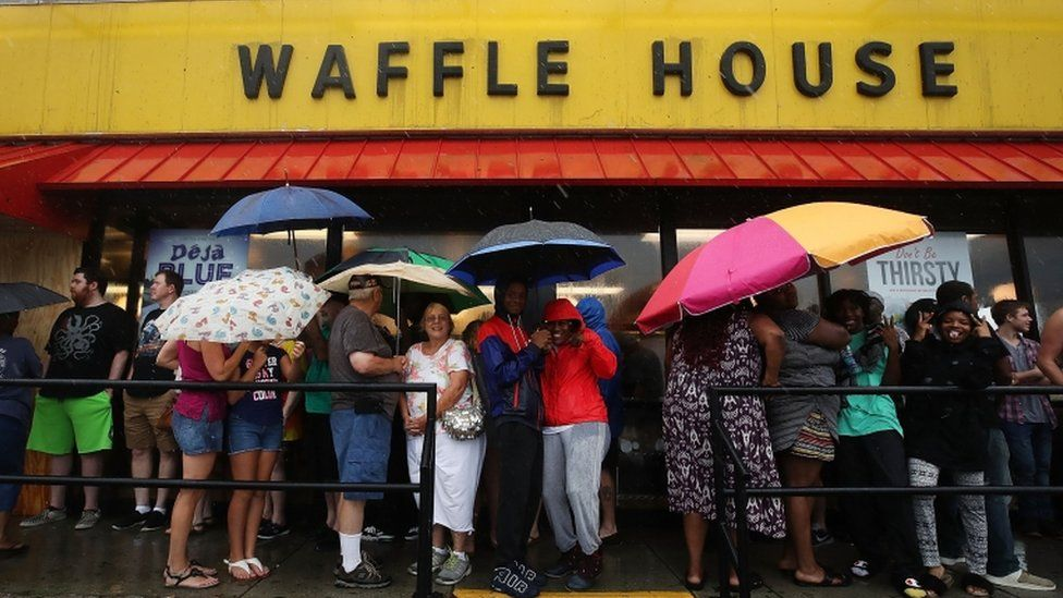 Residents in Wilmington queue holding umbrellas outside a Waffle House