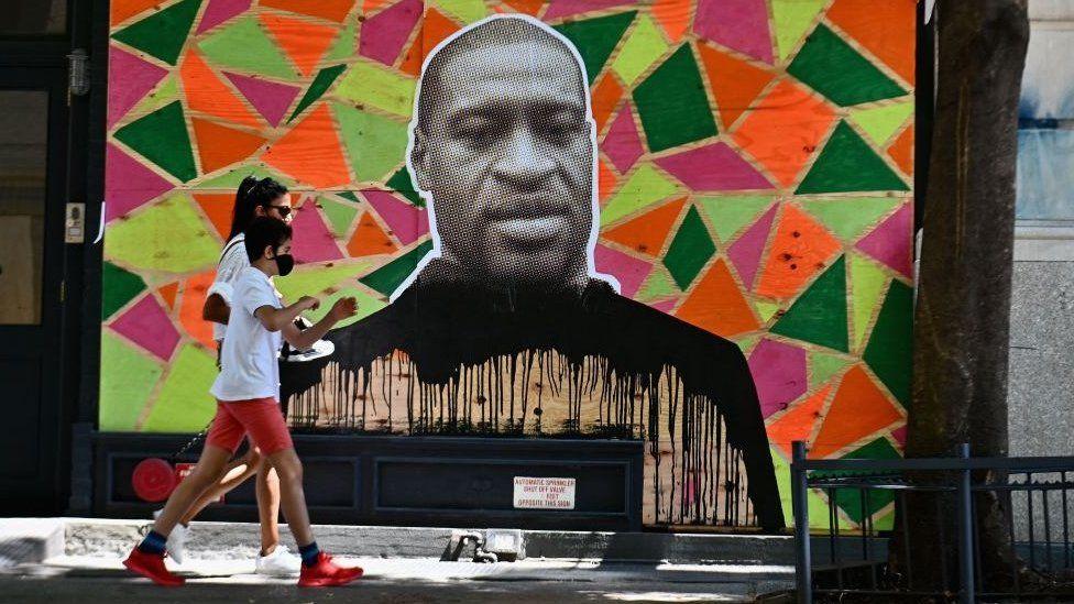 People walk past a mural to George Floyd in New York, June 2020