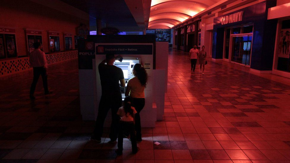 People use an ATM machine at a shopping mall during a power outage in San Juan, Puerto Rico, on 21 September
