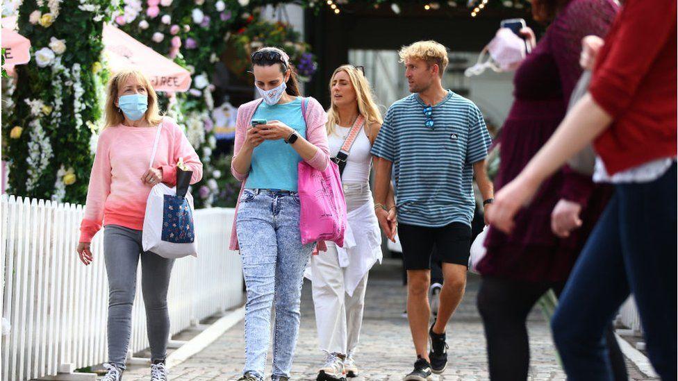 People wearing face masks walking down in public