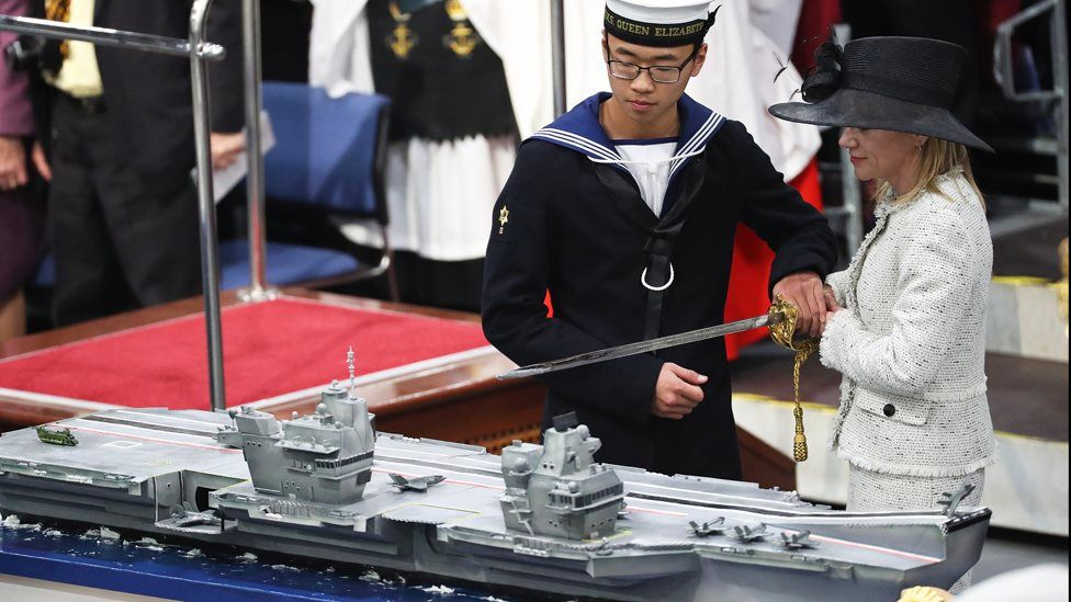 AB Callum Hui and Dr Karen Kyd cutting the cake at the commissioning of HMS Queen Elizabeth.