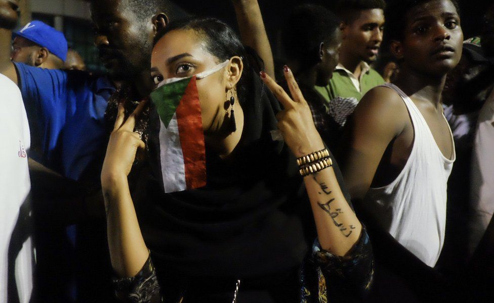 A woman with a Sudanese flag over her face at a sit-in at the military HQ in Khartoum, Sudan - Monday 8 April 2019