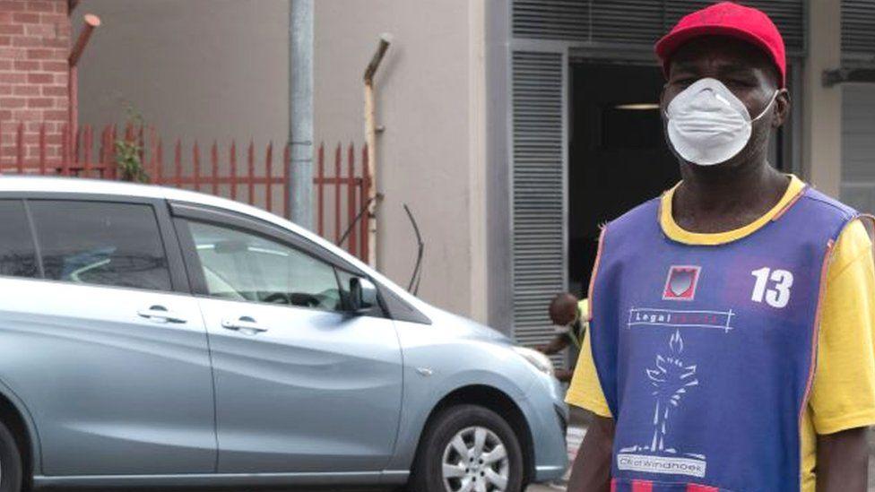 Man with a mask near a car