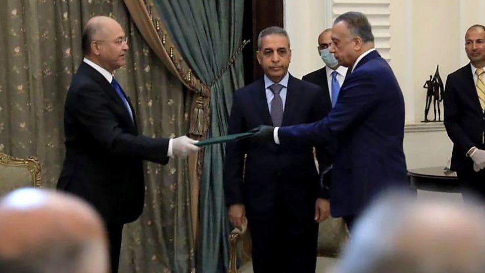 President Barham Saleh (L) and Mostafa al- (R) wore gloves at the ceremony