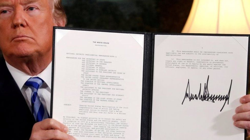 US President Donald Trump holds up a proclamation declaring his intention to withdraw from the JCPOA Iran nuclear agreement after signing it in the Diplomatic Room at the White House in Washington on 8 May 2018.