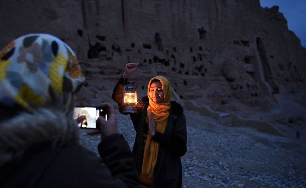 An Afghan woman holding a lantern poses in the dusk against a carved mountainside