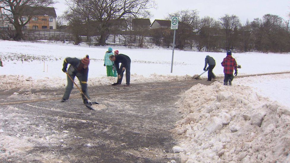 People out clearing snow in Bearsden