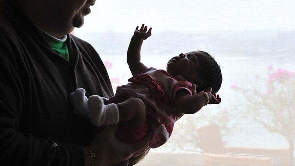 In this 19 February 2010 photograph, US citizen Brad Fister, 29, cradles his 23-day old daughter Ashton in Hyderabad.
