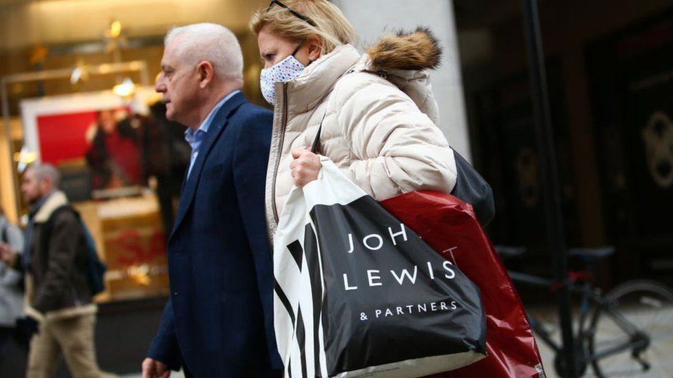 Woman carrying John Lewis shopping bag.