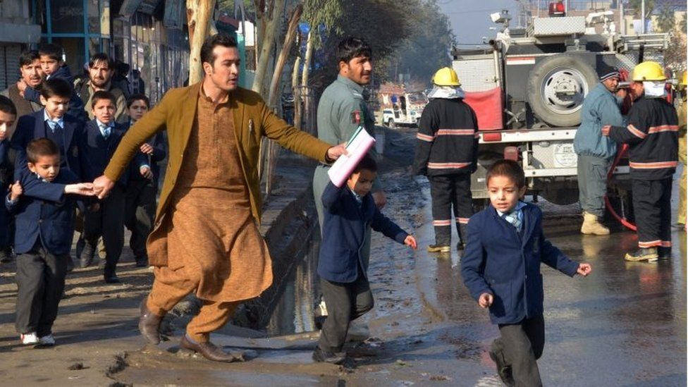 An Afghan teacher, in brown, helps school children run from the site of clashes near the Pakistan consulate in Jalalabad, capital of Nangarhar province, Afghanistan, Wednesday, Jan. 13, 2016.