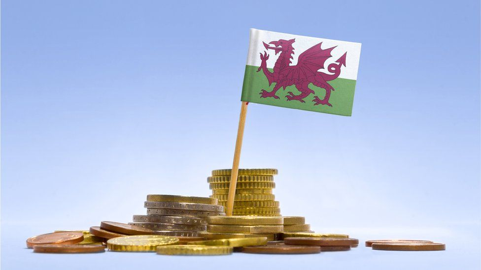 A pile of coins surround a Welsh flag