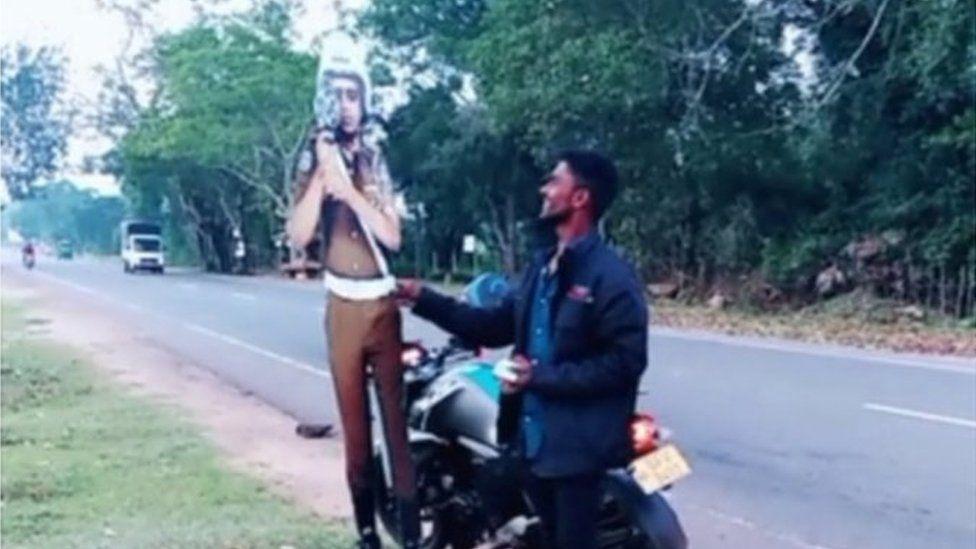 Screen grab from social media video of man bribing life-size cardboard cutout