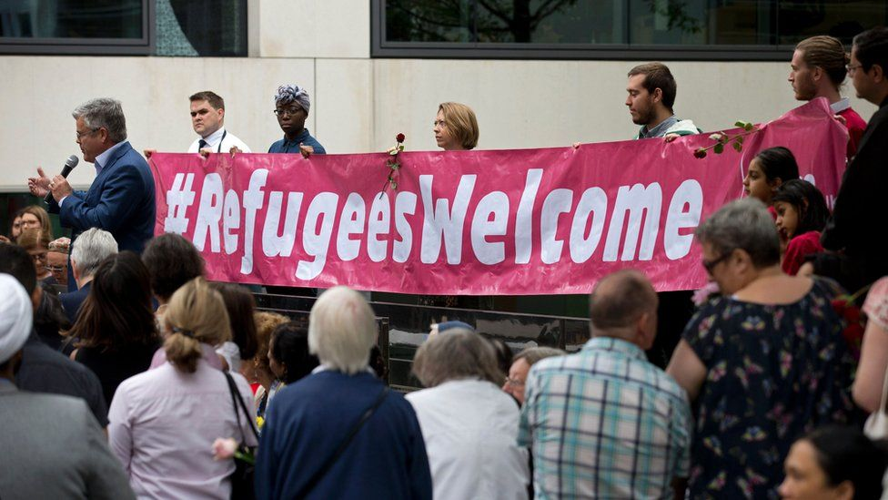 People holding a banner saying 'refugees welcome'