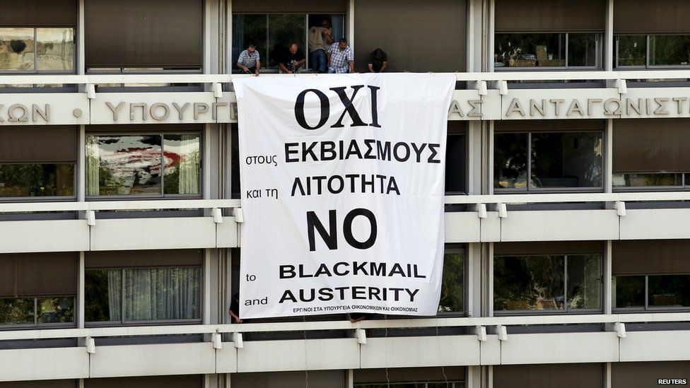 Employees stand by a banner unfolded from a balcony of the Finance Ministry in Athens