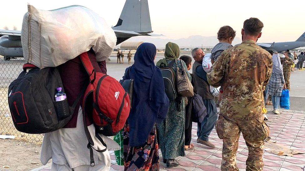 People walking towards planes waiting at Kabul airport