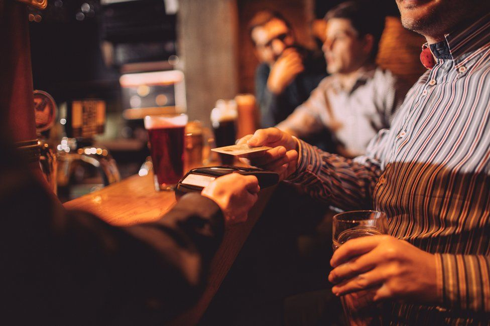 Man paying for drinks in pub with contactless card