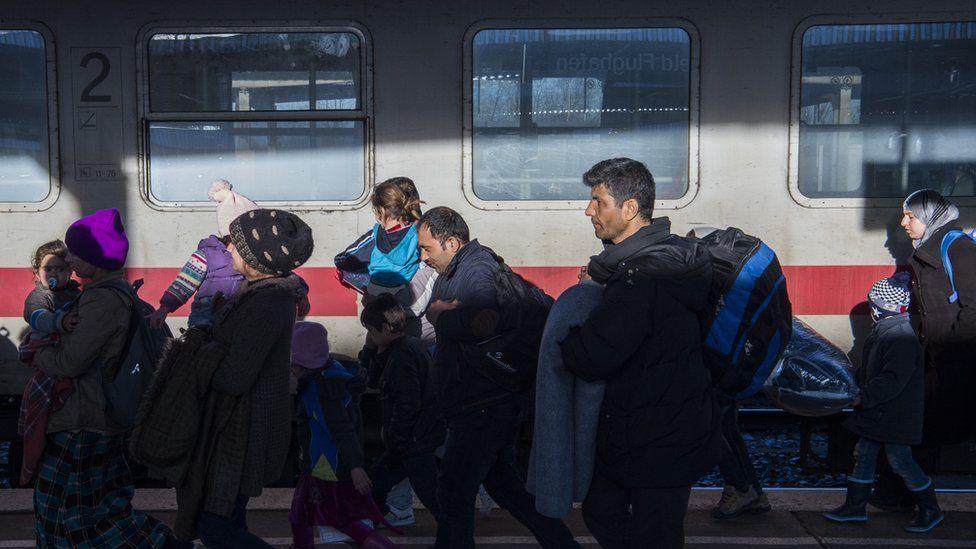 Asylum seekers walk on the platform after getting off a train at the Schoenefeld train station near Berlin on 24 December 2015