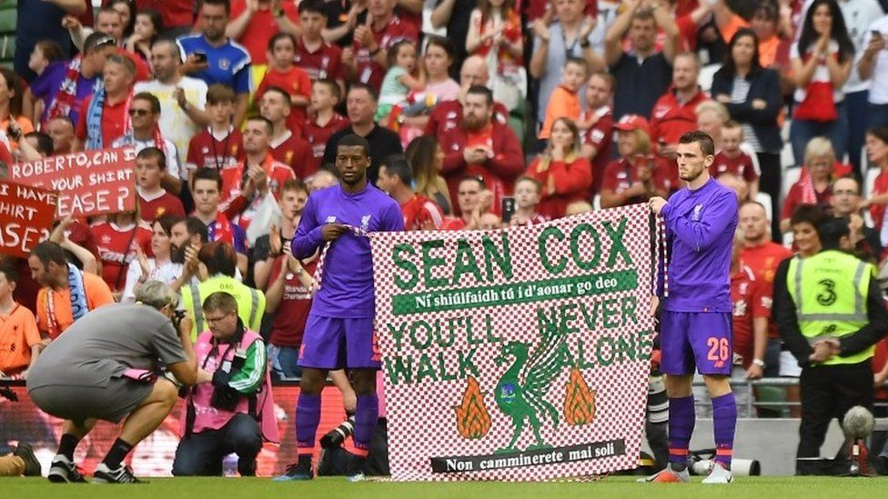 Liverpool's Georginio Wijnaldum and Andrew Robertson hold up a banner in support of Liverpool fan Sean Cox