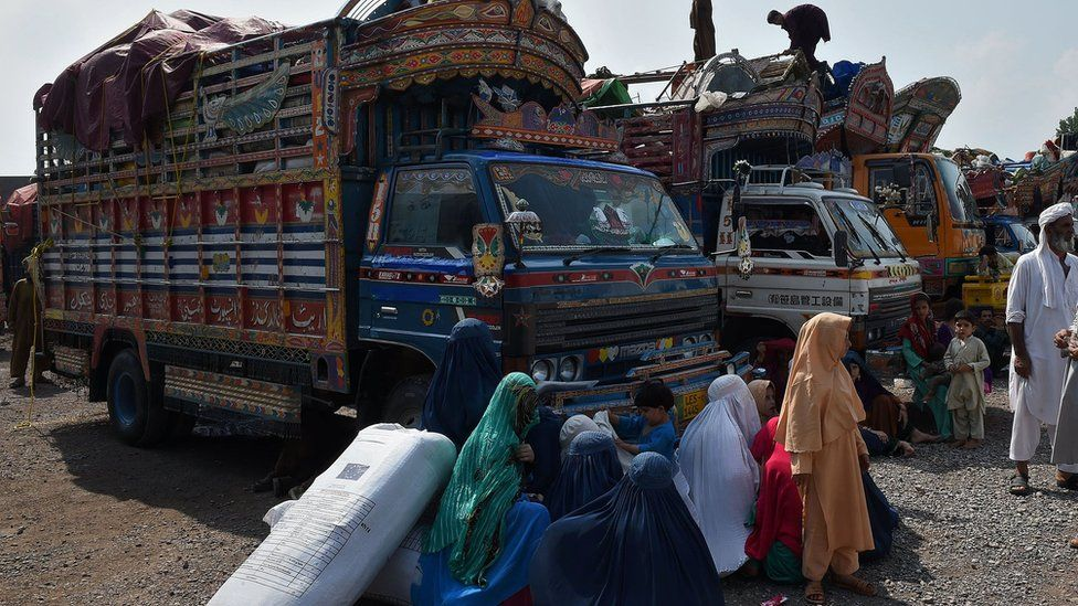 Afghan refugee families wait to board trucks at the United Nations High Commissioner for Refugees (UNHCR) repatriation centre on the outskirts of Peshawar on July 28, 2016,