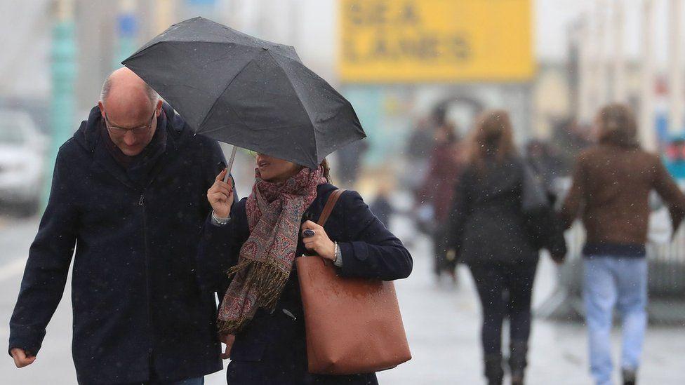 A couple under an umbrella in Brighton