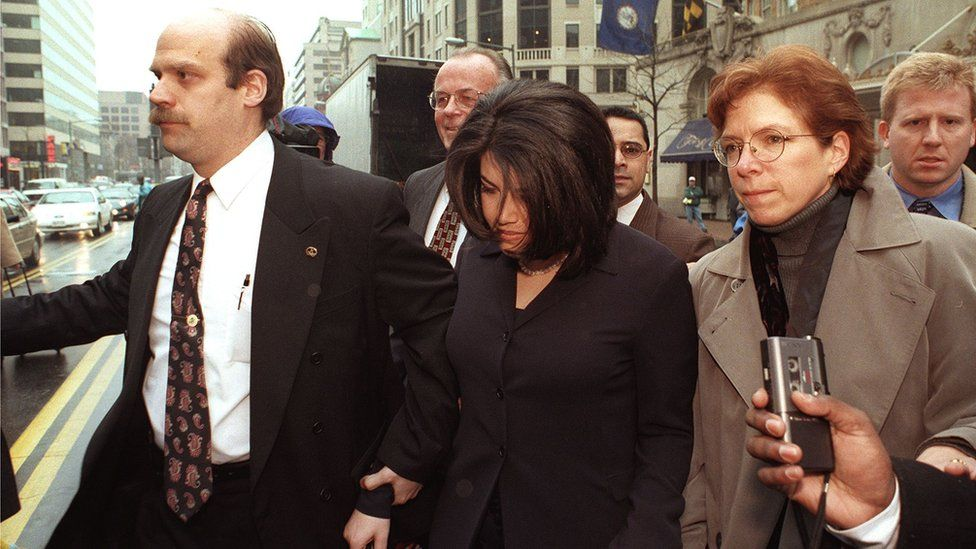 Monica Lewinsky, with her head down, being escorted in 1998 archive shot