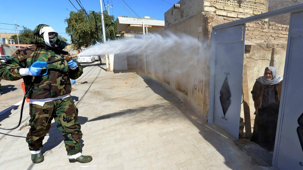 An Iraqi man looks out of a doorway as a civil defence worker disinfects an area of Najaf where Covid-19 cases have been detected (3 February 2020)