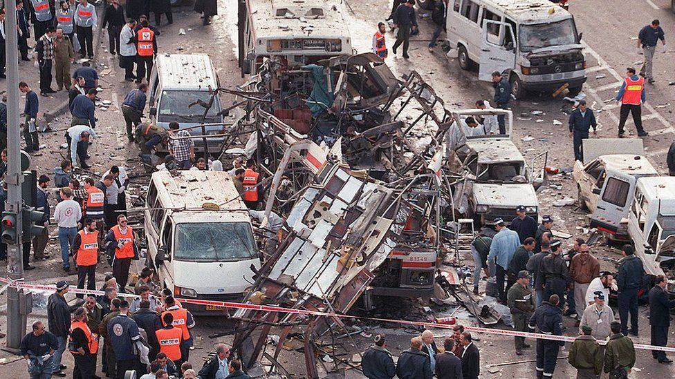 Israeli rescue teams look inside the wreckage of a bus destroyed by a bomb explosion on 25 February 1996 in Jerusalem