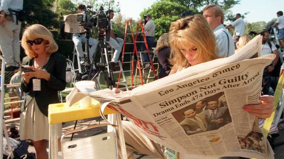 TV reporter Pat Lalama reads a newspaper headlining the not guilty verdicts of O.J. Simpson as she and hundreds of members of the press staked out the Simpson residence in Brentwood, CA.