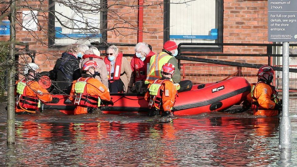 Firefighters transporting people in dinghy
