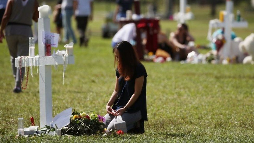 A young girl sits at a temporary memorial in Parkland, Florida. Photo: 17 February 2018