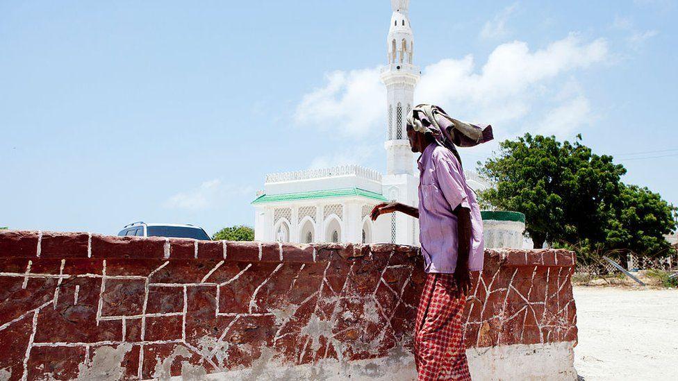 Somali man walks past a mosque