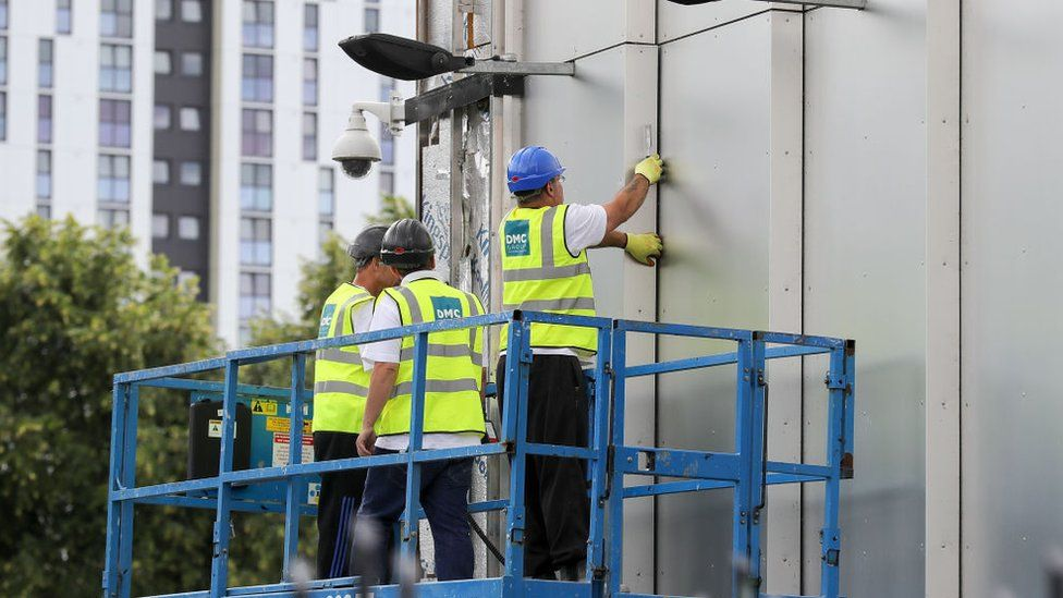 Workers remove cladding from a building