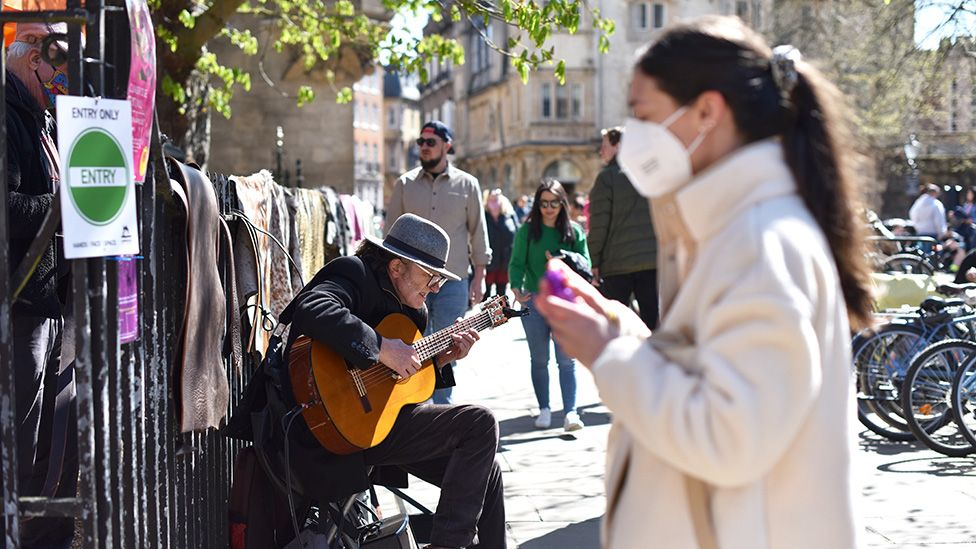 A man plays guitar by the entrance of an arts and craft market on the first weekend since the easing of lockdown restrictions in Cambridge, England - April 17, 2021