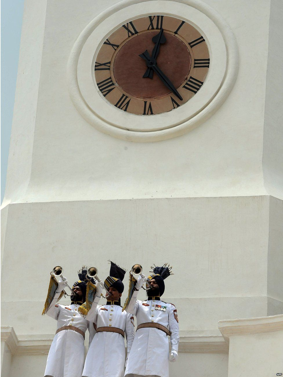 Indian President's ceremonial guards blow trumpets during the inauguration by President Pranab Mukherjee of a restored clock tower inside The President's Estate in New Delhi on 24 July 2015, to mark the completion of the third year of his presidency.