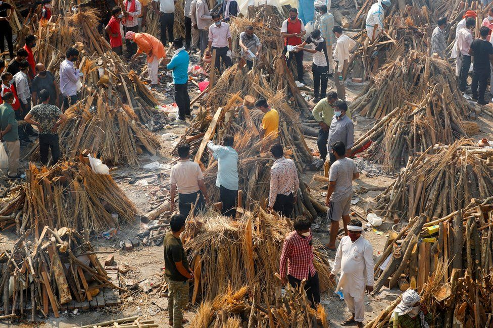 People prepare funeral pyres for a mass cremation in New Delhi, India